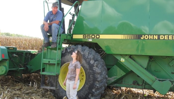James Adkins and Amy Shober in a field with a green tractor