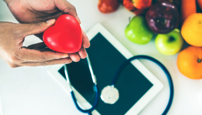 Hands holding a heart shaped toy near fresh fruit and stethoscope