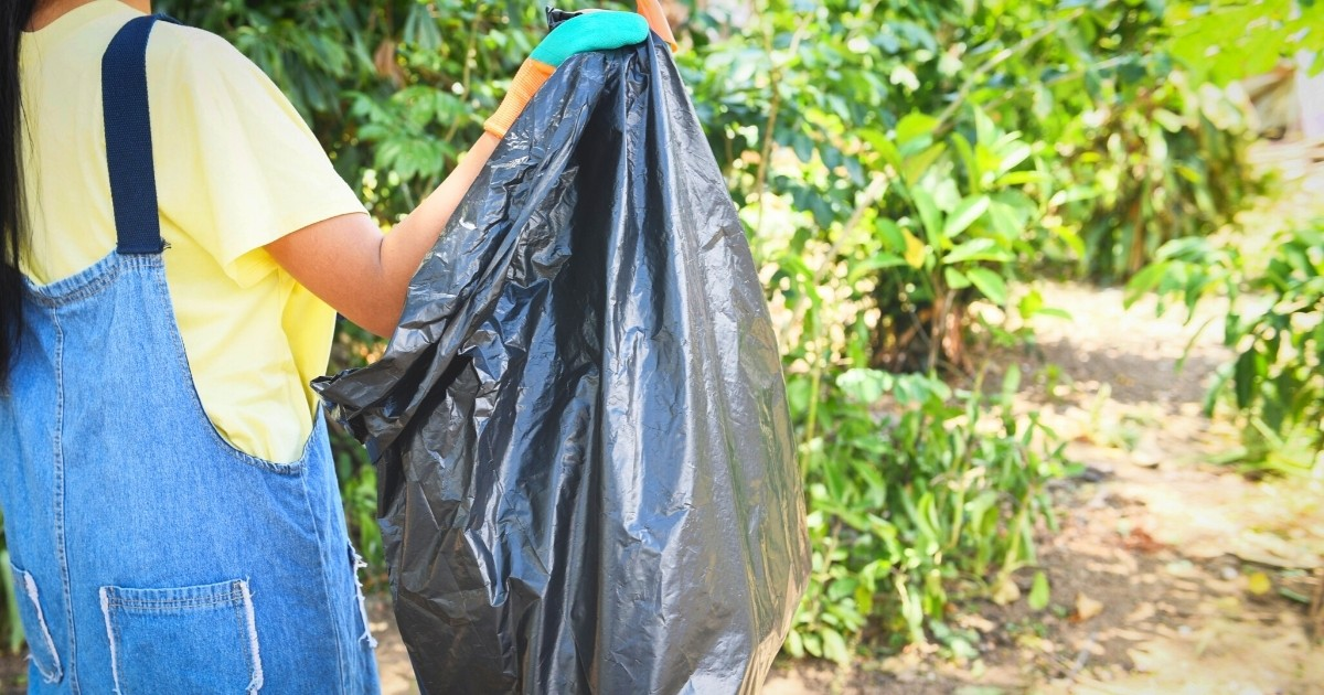 A 4-H'er holds a garbage bag while cleaning up at a park.