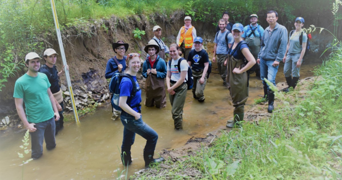 Grant Jiang and Nate Sienkiewicz (center) in cowboy hats along with other researchers and students along a legacy sediment streambank.