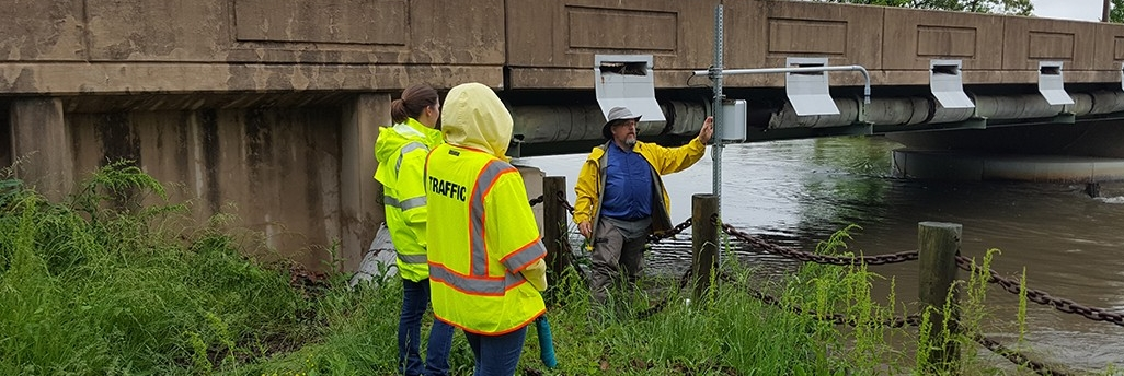 Standing by sensing equipment next to a creek below a bridge, David Huntley of the Center for Environmental Monitoring and Analysis explains low-cost flood sensors he and his team built in a pilot for the Delaware Department of Transportation.