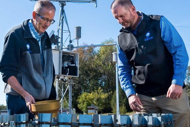 State climatologist Dan Leathers (left) and Kevin Brinson examine monitoring equipment.