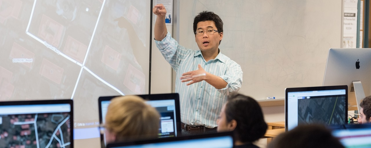 instructor at front of classroom with students in front of computers showing GIS software