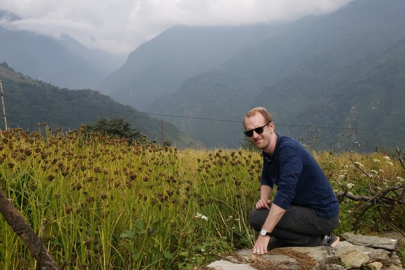 UD assistant professor Kyle Davis sits near a millet field in the Himalayan foothills.