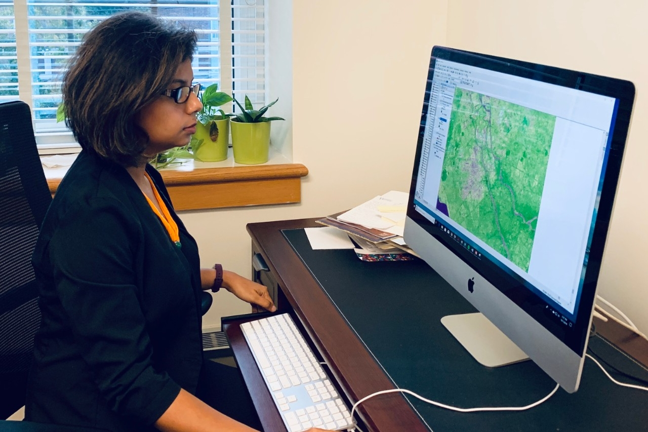 Professor Pinki Mondal at computer with GIS showing