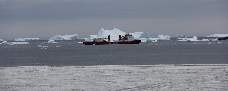ship in front of iceberg