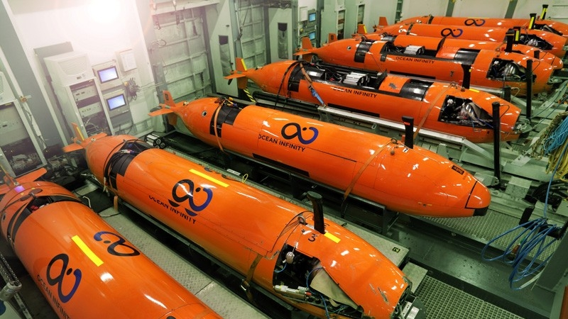 Ocean Infinity employees move autonomous underwater vehicles in the company's building.