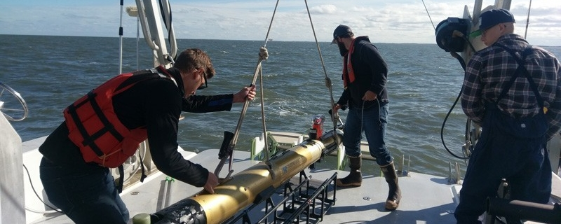 Students prepare to deploy an autonomous underwater vehicle from the stern of the R/V Joanne Daiber