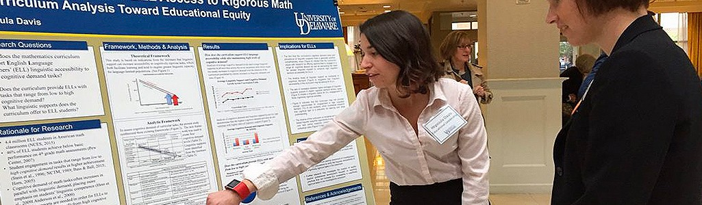 A graduate student explains her poster presentation at a conference.