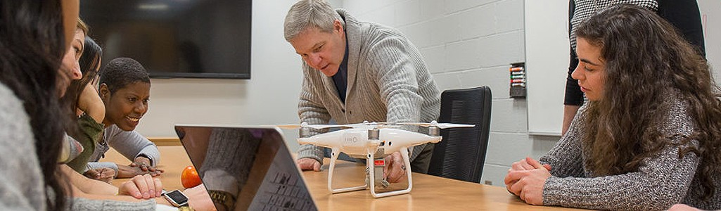 A professor and students in a classroom discussing a drone being used for research.