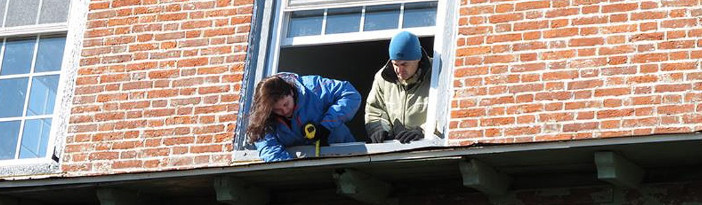 View from below looking up at two students as they lean out of a window and work on restoring a brick building.