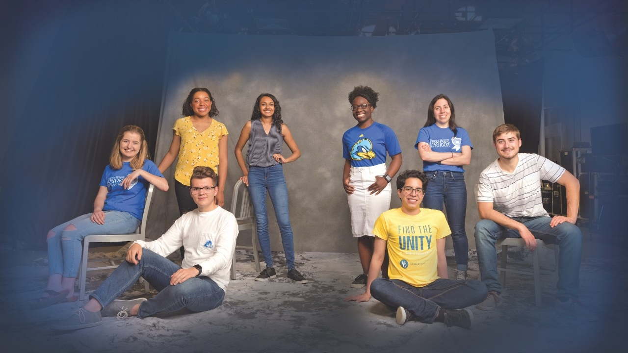 university of delaware honors students posing in front of a backdrop