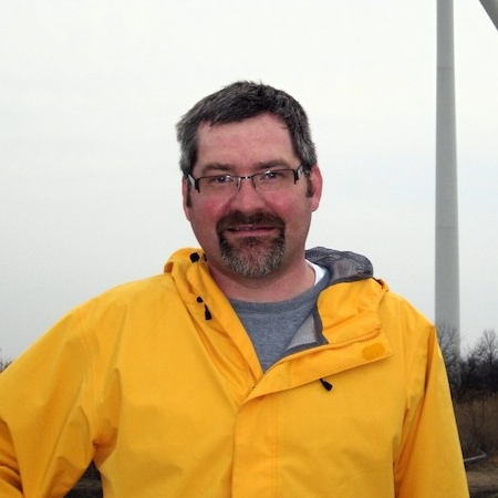 Photo of faculty member Jeffrey Buler near a wind turbine