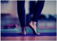 Background photo showing a person standing on a yoga mat practicing mindfulness.