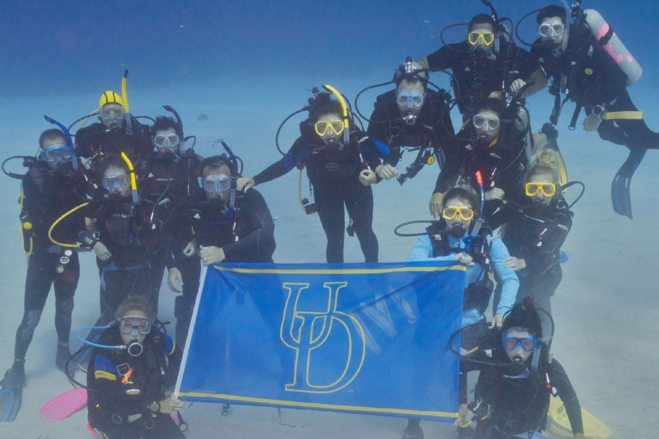 Scuba Diving Students Hold UD Flag