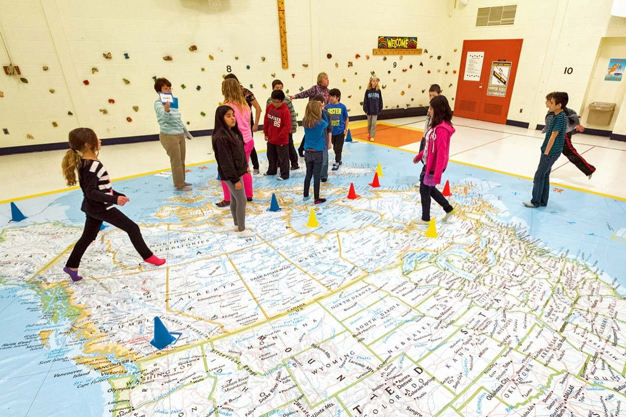 Elementary school students explore a giant map of the US and Canada.