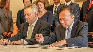 A photo of President Assanis and a member of the XMU delegation signing an agreement.