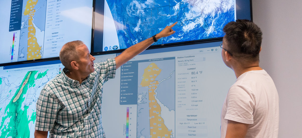 professor and student at the University of Delaware working in the meteorology visualization lab in Pearson hall