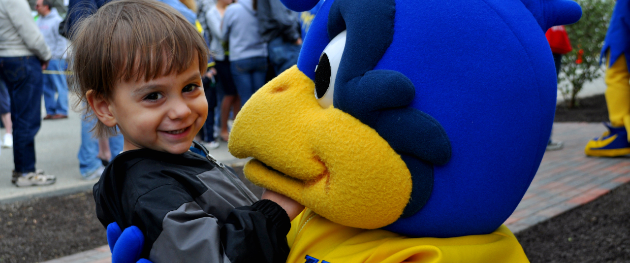 Smiling boy with University of Delaware mascot YouDee