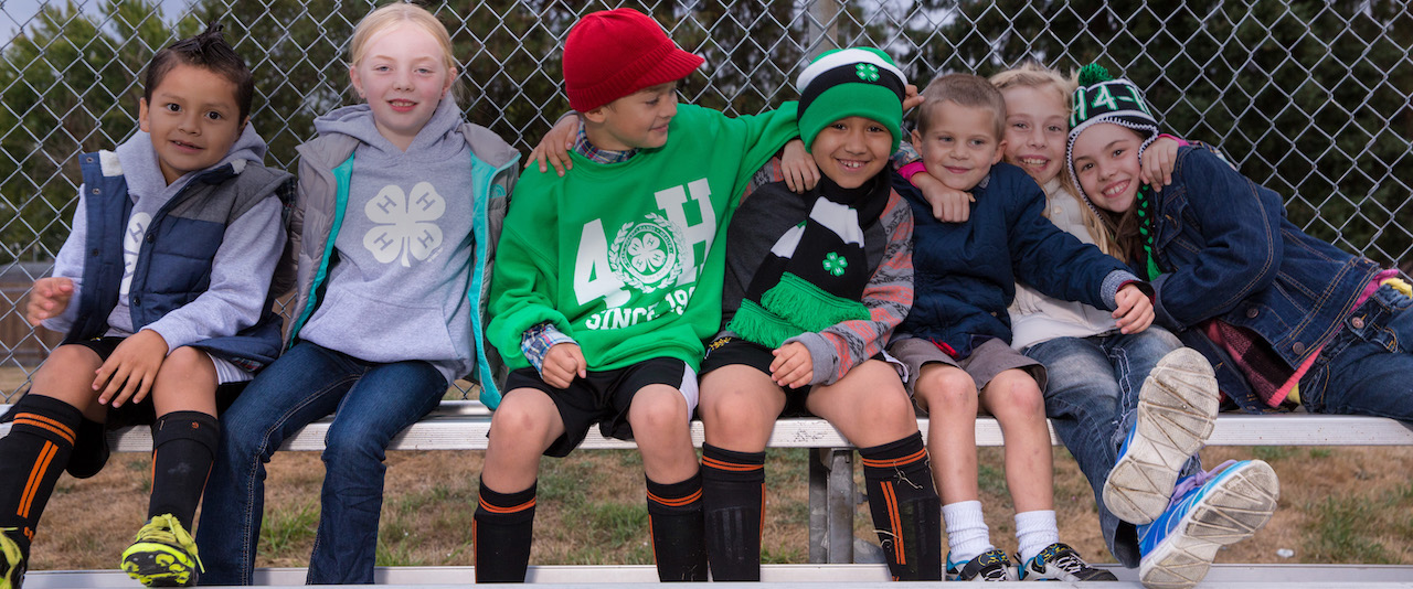 Kids sporting 4-H-branded gear sit on a bench with their arms around each other.