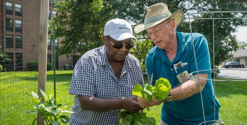 Master Gardener volunteer educator Rick Judd and Main Towers resident Gail Brison work in the community garden.