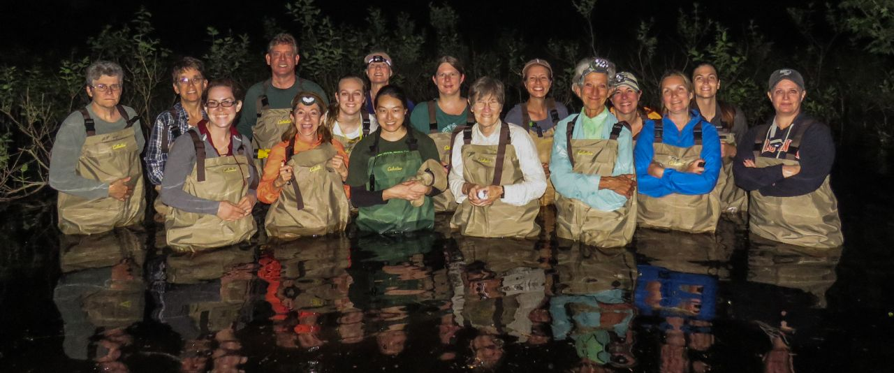 A master naturalist class stands in their waders in a pond to pose for a photo.
