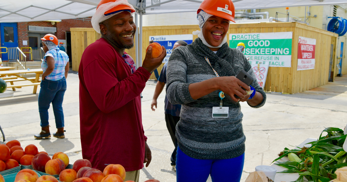 Two Perdue employees enjoy fresh fruit on a hot summer day at a worksite farmer's market.