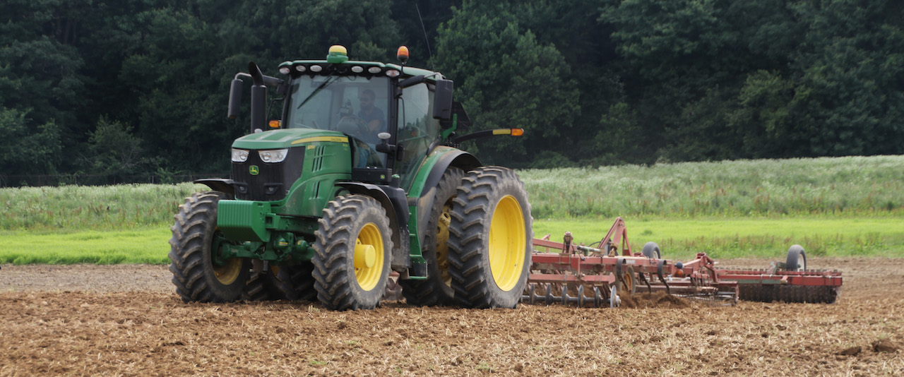 A photo of a Delaware farmer in his John Deere tractor grading a field.