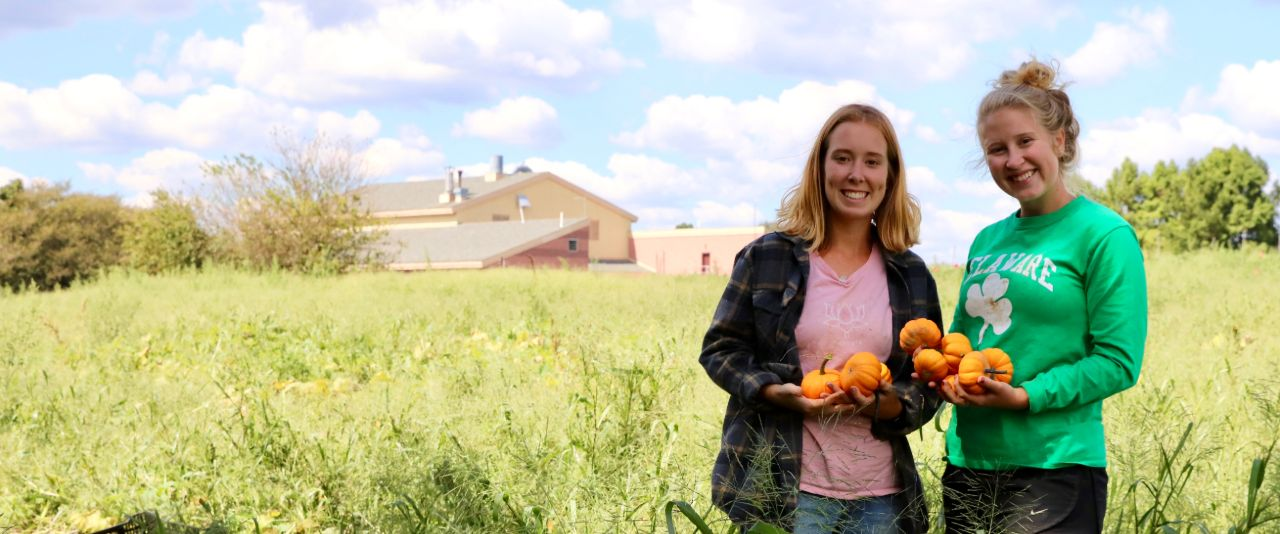 Caroline May and Summer Thomas hold pumpkins in the organic farm field