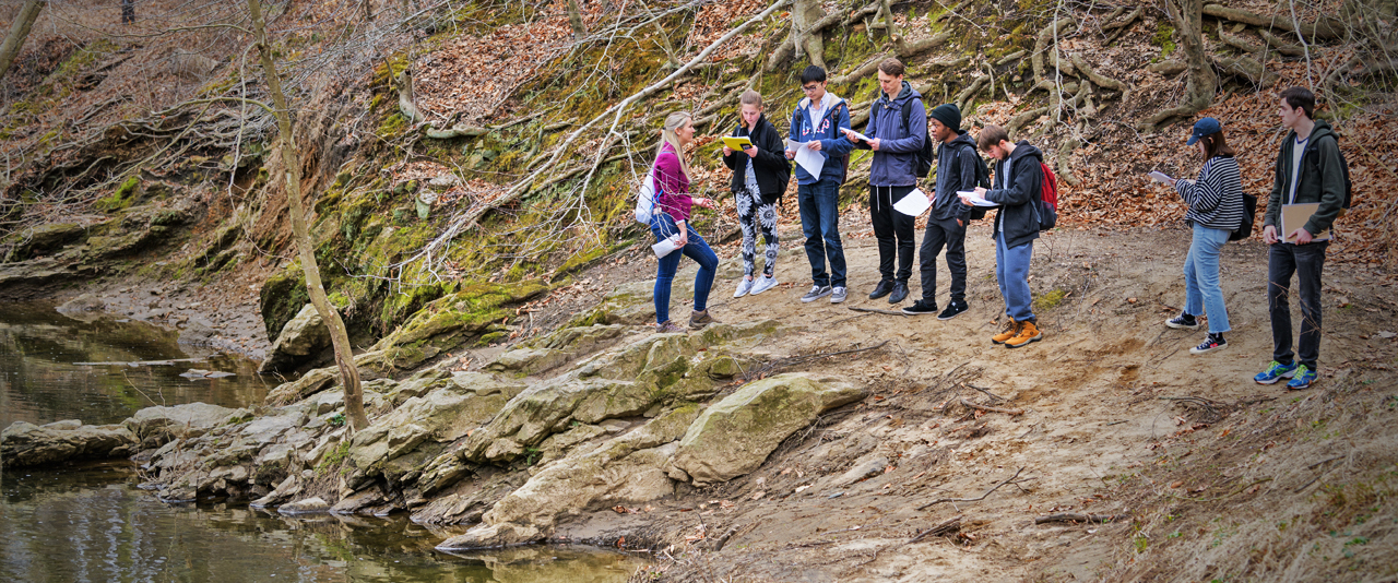 Group of students examines creek formations during an outdoor excursion in a earth sciences class
