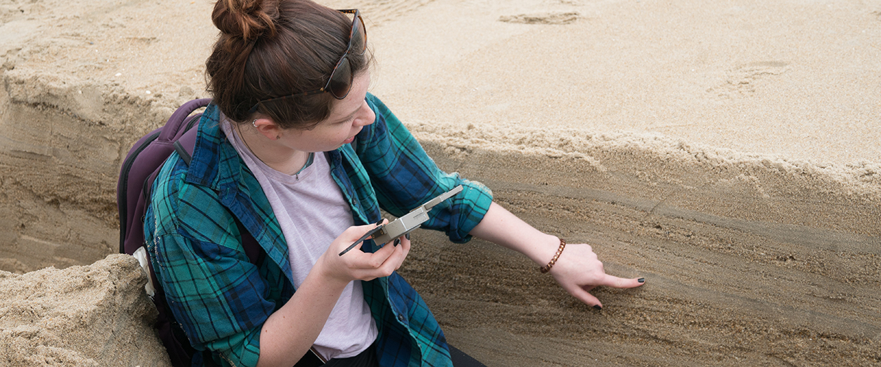 Geology student Natalie Zimmerman measuring orientation and slope of sand layers in a trench at Cape Henlopen.