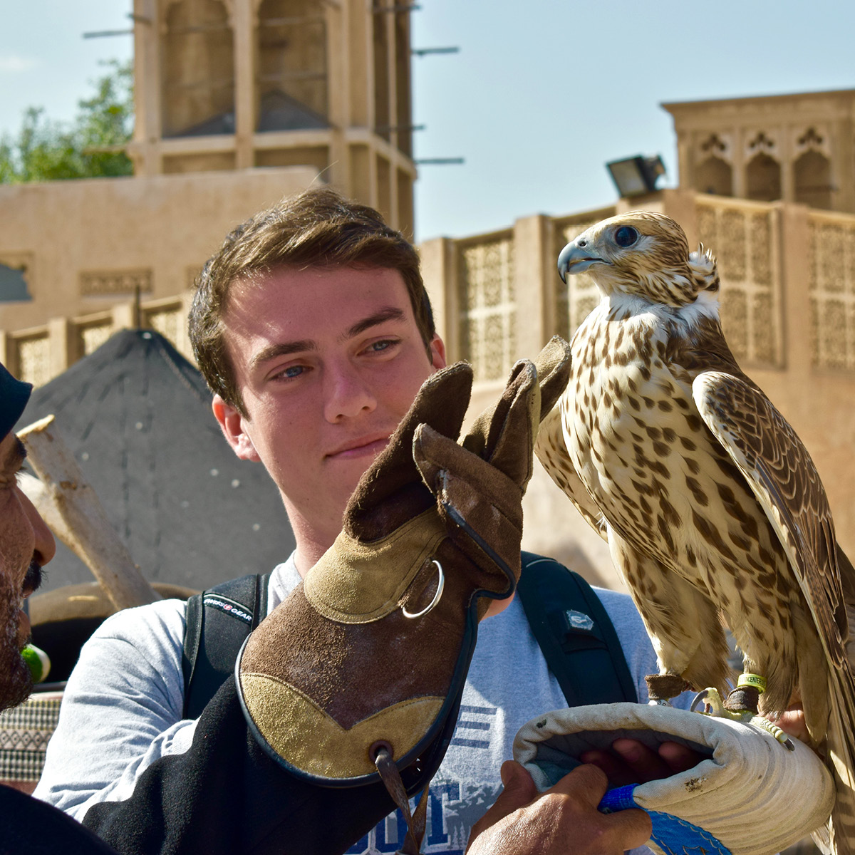 A UD student stands alongside a falcon and its trainer.