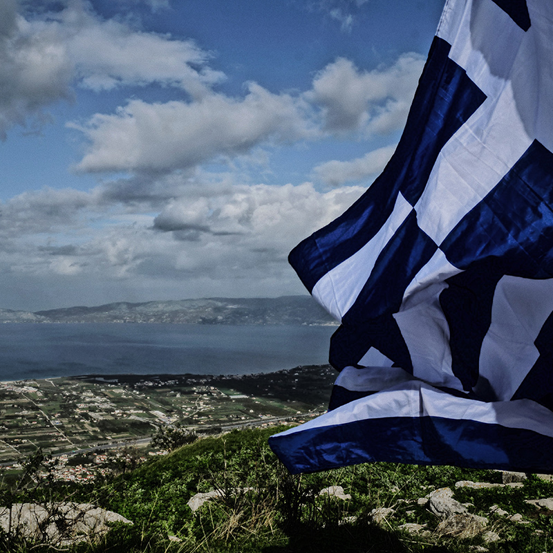 A view of Athens with a waving Greek flag.