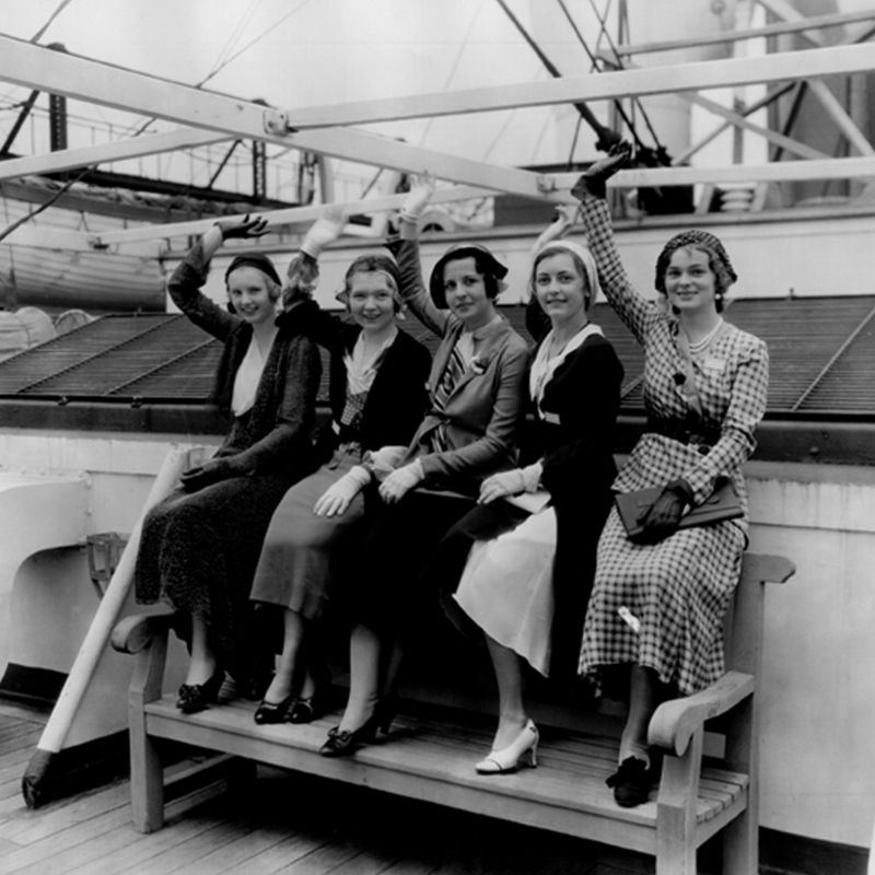A black and white historic images of five women waving on a ship.