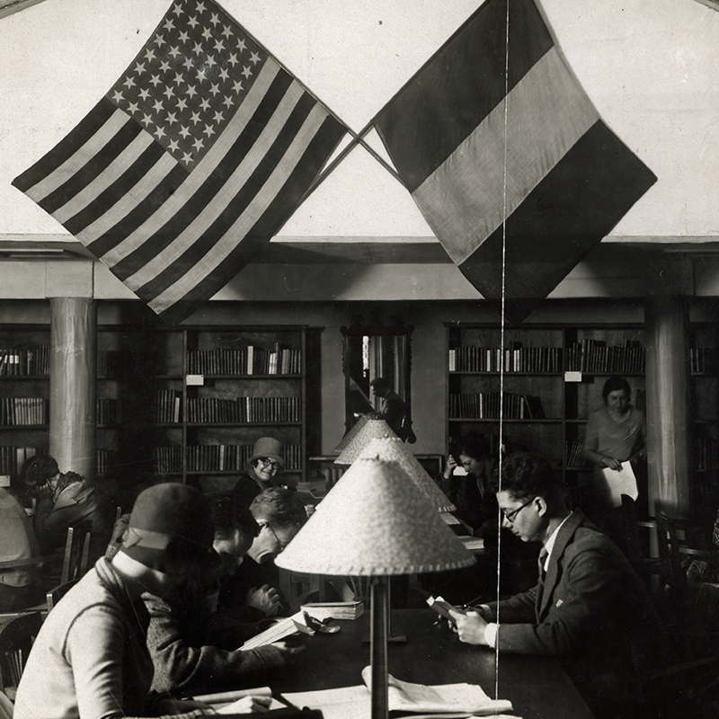 A black and white historic image of two students studying at a desk with the American and French flags above.