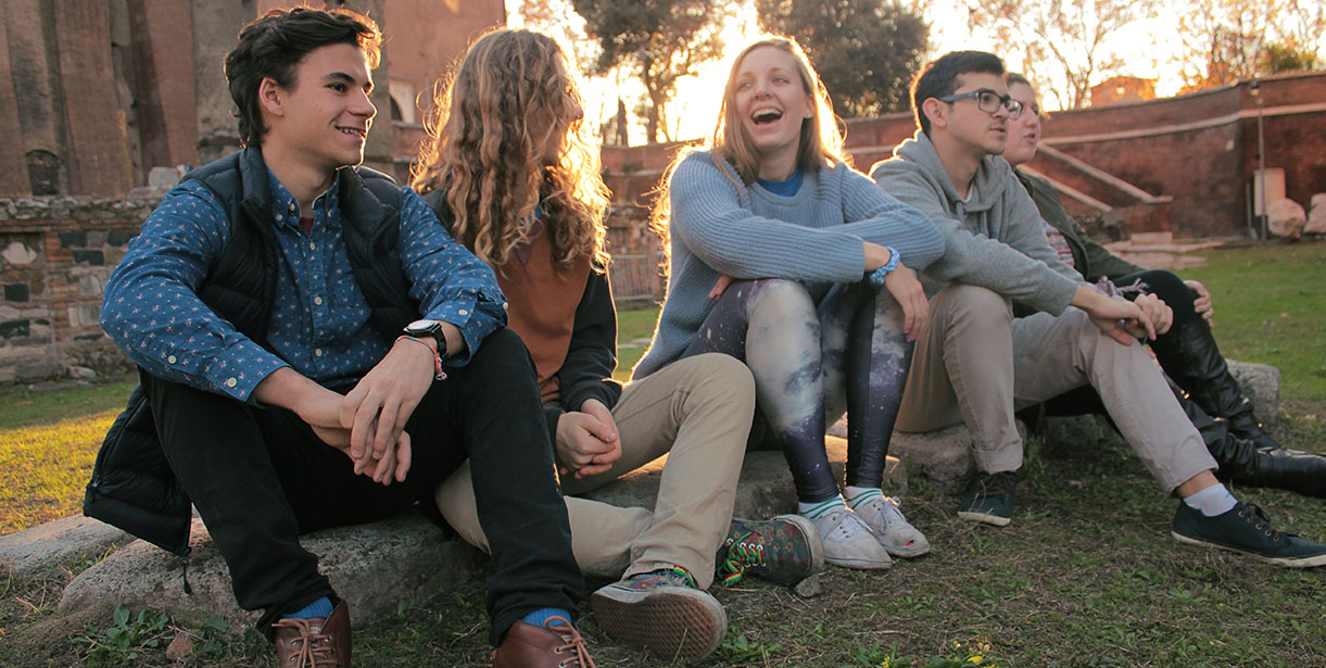 Five UD World Scholars sit in front of the Colosseum during Golden Hour.
