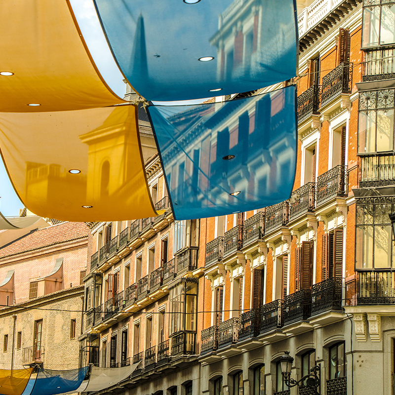 A view of blue and gold flags hanging from the street in the Plaza del Sol, Madrid.