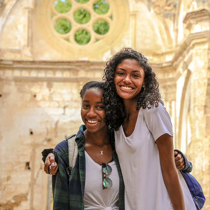 Two UD students hug each other for a photo at an ancient monastery