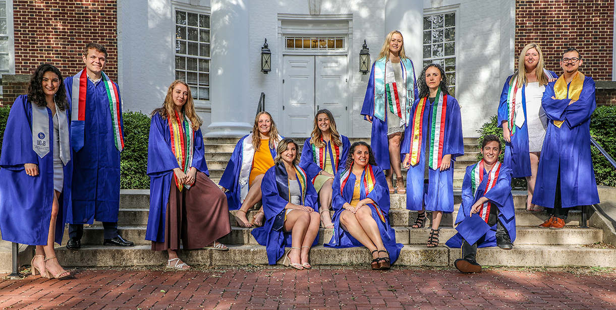 UD World Scholars stand and sit for a photo in their graduation regalia.