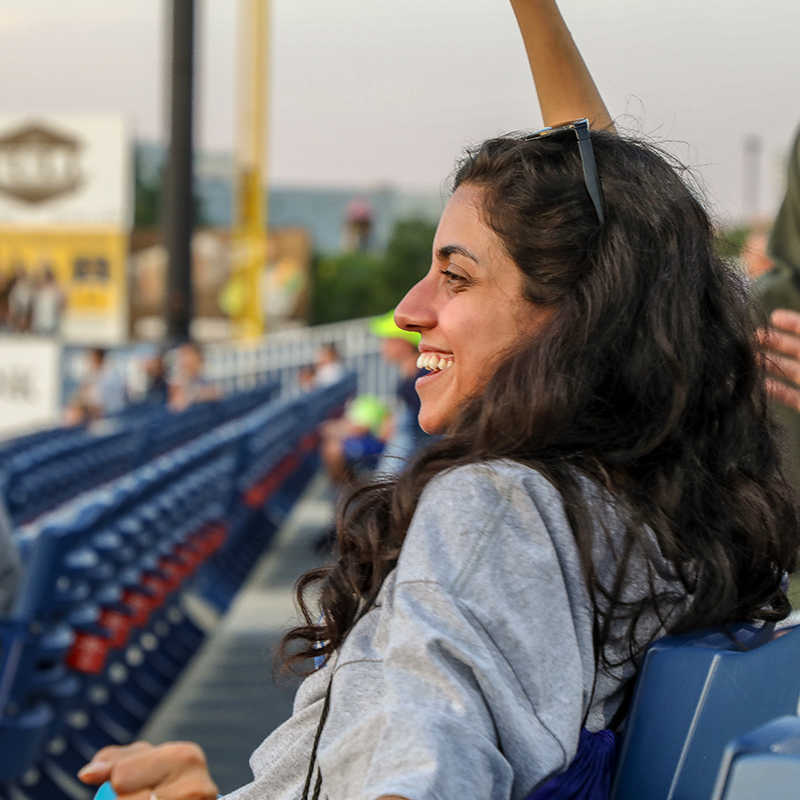A MEPI Student Leader cheers at a baseball game.