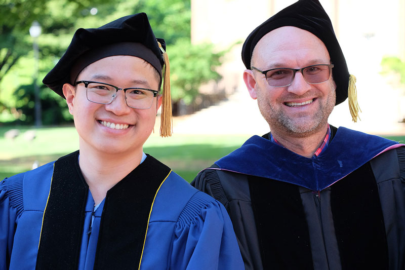 Two doctoral hooding event attendees