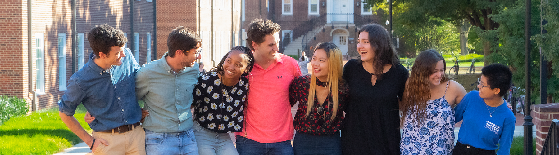 A group of diverse students with arms around their shoulders, laughing and smiling.