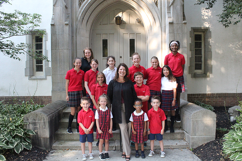 Trisha Medeiros (center), University of Delaware alumna and president of Ursuline Academy, with students from Ursuline's Upper, Middle and Lower Schools, including her son, Mack (at right).