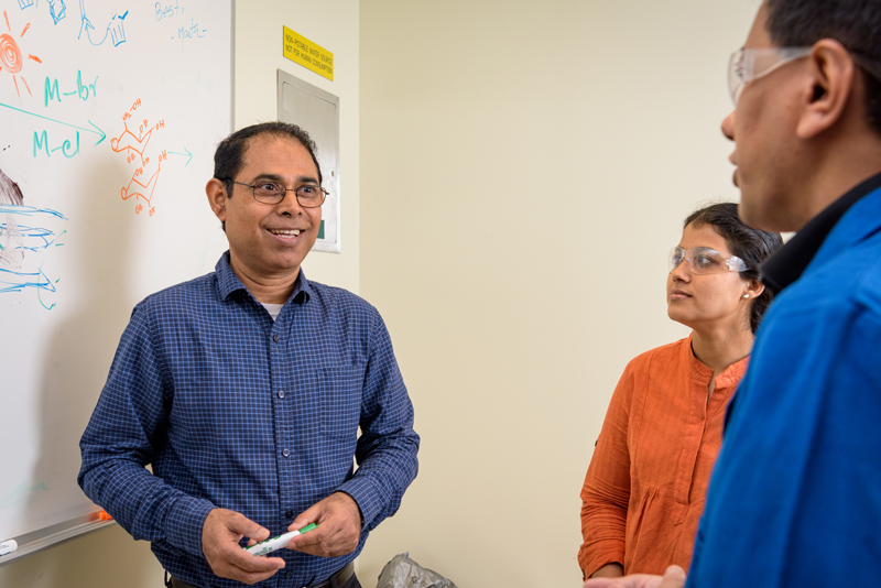 Basudeb Saha, the associate director of research for the Catalysis Center for Energy Innovation, speaking with colleagues Sunitha Sadula and Saikat Dutta.