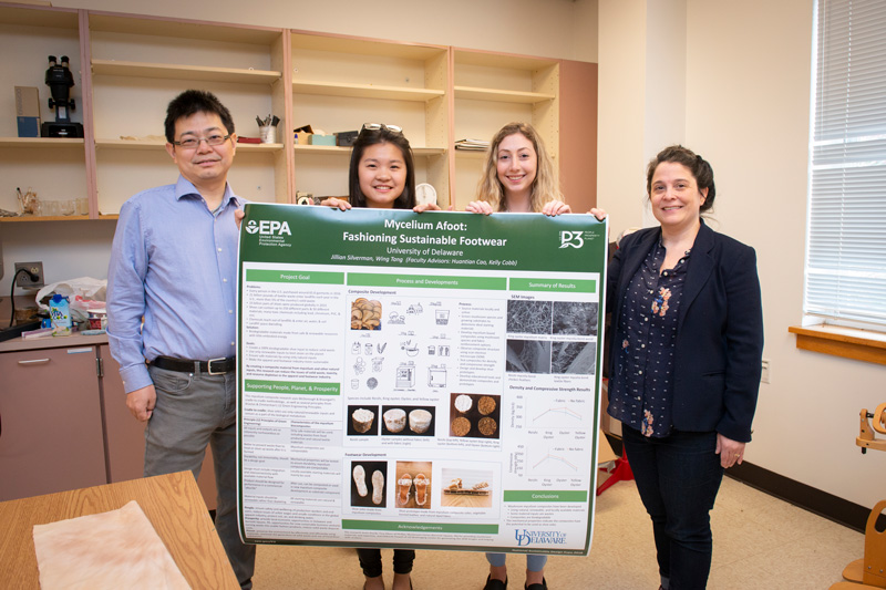 Researchers (from left) Huantian Cao, Wing Tang, Jillian Silverman and Kelly Cobb hold the poster they displayed at their booth at the National Sustainable Design Expo in Washington, D.C.