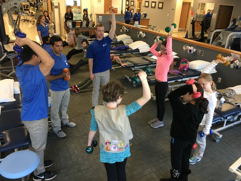 From left to right: Physical therapy graduate students Naoaki Ito, Corey Henley and Kyle Wyss show Girl Scouts a strength exercise.