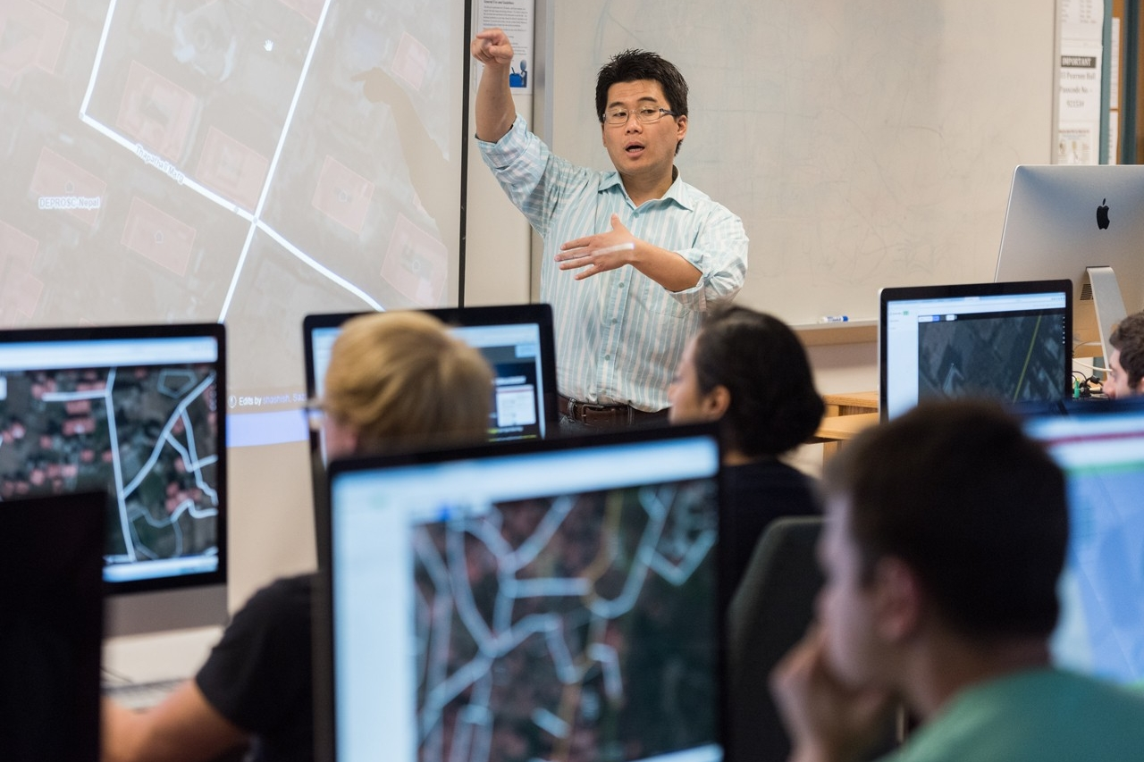 instructor at front of classroom with students looking at computers with GIS software displayed