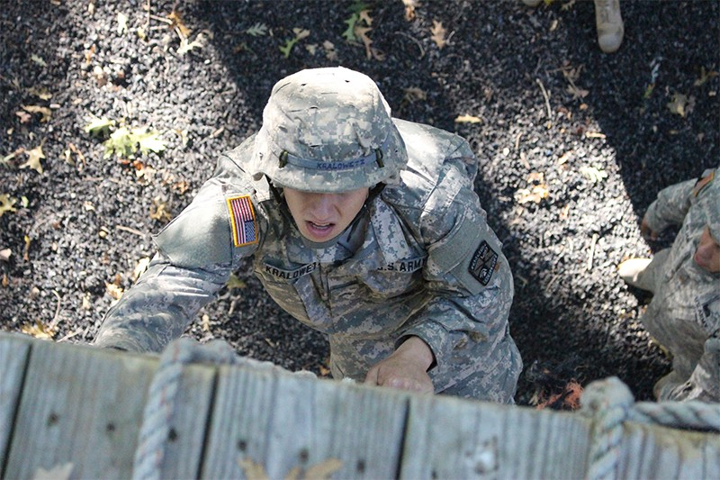 Army ROTC student scales a rope wall in training.