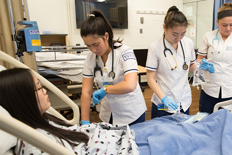 Three female Munson fellow standing side by side in front of a residence hall.