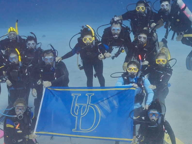 Students posing with a UD flag underwater
